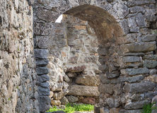 Castel ruin arch of gray stone old building way out of it on a stone masonry labyrinth amid the ruins Stock Images