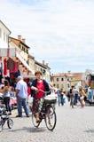 Castelfranco Veneto, Italia - 20 luglio 2018: donna anziana in bici che va al mercato tradizionale fare drogheria in piccola vecc fotografia stock libera da diritti