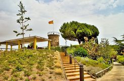 Esplanade with tower and flag of Spain in Parc del Castell in Malgrat de Mar. Castell Park playgrounds, walkways and botanical themed routes. Place of the Stock Image