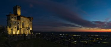 Wide view of the Savorgnan's Castle in Artegna. Friuli, after the sunset blue hour with the lights of the plain in the background stock images