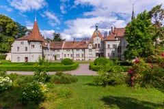 Castello antico con le torri, il campanile ed i cespugli di rose nella priorità alta Fotografia Stock