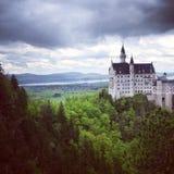 Castello del Neuschwanstein: Cieli nuvolosi drammatici con il villaggio nel fondo Immagine Stock Libera da Diritti