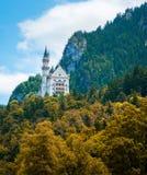 Castello del Neuschwanstein con la foresta di autunno come priorità alta Fotografia Stock