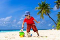 Castello della sabbia della costruzione del bambino sulla spiaggia tropicale Immagini Stock