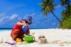 Castello della sabbia della costruzione del bambino sulla spiaggia tropicale Fotografie Stock