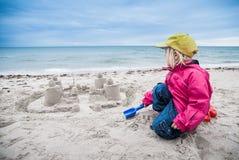 Castello della sabbia della costruzione del bambino vicino all'oceano Fotografie Stock Libere da Diritti