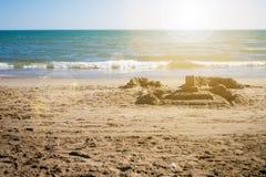 Castello della sabbia sulla spiaggia Tempo di festa e di estate distendasi Il Sun è brillante sopra il livello del mare Fotografia Stock