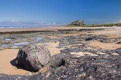 Castello di Bamburgh con le rocce Fotografie Stock Libere da Diritti