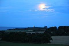 Castello di Dunstanburgh alla notte Fotografia Stock