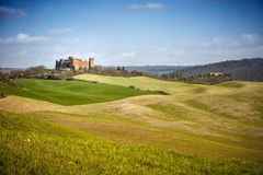 View of Castle of Gallico. Beautiful landscape of hills and fields near Asciano in Tuscany, Siena, Italy. The Castello di Gallico, with its five stone and red royalty free stock images