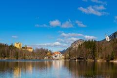 Castello di Hohenschwangau, vista del lago Alpsee, paesaggio in primavera, fogliame di caduta dell'acero rosso, Baviera, Germania Immagini Stock Libere da Diritti