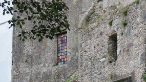 Castello di lusinga e una finestra di vetro macchiato variopinta fotografia stock libera da diritti