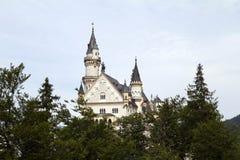 Castello di Neuschwanstein fra gli alberi Immagini Stock Libere da Diritti