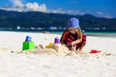 Castello di sabbia della costruzione del bambino sulla spiaggia Fotografie Stock Libere da Diritti
