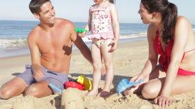 Castello di sabbia della costruzione della famiglia sulla spiaggia archivi video
