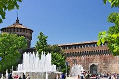 Castello di Sforza a Milano I mura di mattoni rossi e la torre Molta gente cammina vicino al castello Nella priorità alta la font fotografia stock libera da diritti