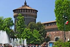 Castello di Sforza a Milano I mura di mattoni rossi e la torre Molta gente cammina vicino al castello Nella priorit? alta la font fotografia stock libera da diritti
