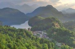 Castello e villaggio di Hohenschwangau, in mezzo dei laghi, al tramonto Fotografie Stock Libere da Diritti