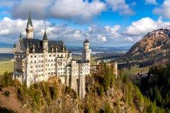 Castello famoso del Neuschwanstein nelle montagne e negli alberi delle alpi del fondo Fussen, Baviera, Germania Immagini Stock