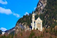 Castello famoso del Neuschwanstein nelle montagne e negli alberi delle alpi del fondo Fussen, Baviera, Germania Immagine Stock