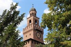 Castello Sforzesco Milan Italy, en sikt på det huvudsakliga tornet mellan träden Royaltyfria Bilder