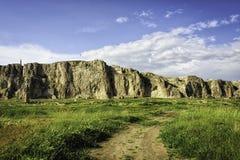 Castello storico su una collina con le nuvole lanuginose pianta e strada non asfaltata dei cieli blu Immagine Stock Libera da Diritti
