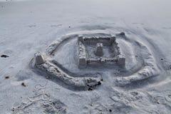 Castello via parzialmente lavato della sabbia sulla spiaggia Immagini Stock