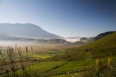 Castelluccio二诺尔恰翁布里亚看法在黎明,与薄雾,大草甸和完全倒空蓝天 免版税图库摄影