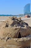 Castelo da areia na praia com construções do fundo Imagens de Stock Royalty Free