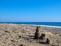 Castelo de areia na praia, mar bonito calmo foto de stock