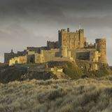 Castelo de Bamburgh em Northumberland no por do sol Fotografia de Stock Royalty Free
