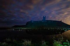 Castelo de Dunstanburgh na noite fotografia de stock royalty free