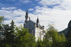 Castelo de Neuschwanstein entre árvores verdes, cumes bávaros Imagem de Stock Royalty Free