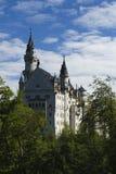 Castelo de Neuschwanstein entre árvores verdes, cumes bávaros Fotos de Stock