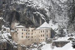 Castelo de Predjama na caverna de Postojna, no inverno fotografia de stock