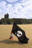 Castelo e praia com a bandeira alegre de Roger Fotografia de Stock