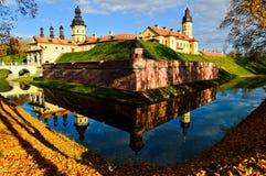 Castelo medieval velho, antigo com spiers e torres, paredes da pedra e tijolo cercado por um fosso protetor com água imagem de stock royalty free