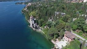 Castelo Panorama do lago lindo Garda cercado por montanhas, Itália Tiro video com zangão filme