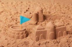 Castelos feitos da areia, do Colosseum e da bandeira azul na areia imagem de stock