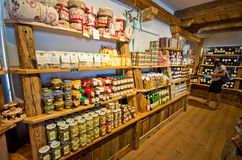 Castelrotto speck shop interior. The interior of a small speck shop of Italian Castelrotto (Kastelruth). Shelves with local food products and specialties. Woman Stock Image