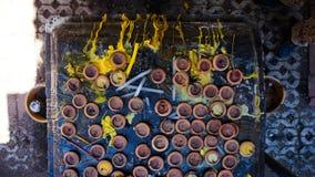 Castiçais e cera do amarelo em um santuário da Buda Fotografia de Stock Royalty Free