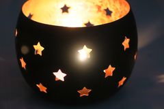 Castiçal com as estrelas pretas que irradiam a luz do interior imagens de stock royalty free