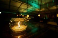 Castiçal de vidro com uma vela ardente imagem de stock