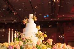 Castiçal e bolo de casamento na tabela de vidro na fase na cerimônia de casamento Conceito das ferramentas e das decorações da ce Fotografia de Stock Royalty Free