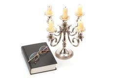 Castiçal, livro e vidros foto de stock