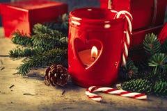 Castiçal vermelho com as caixas de presentes atuais no fundo de madeira Imagem de Stock Royalty Free