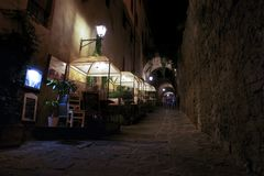 Tourist have dinner in the street at night. In the territory of Castiglione della Pescaia royalty free stock photo