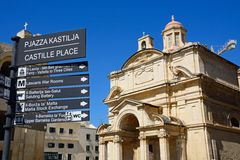 Castille Place signpost and St Catherine of Italy Church, Valletta. Castille Place signpost with St Catherine of Italy church to the rear in Castille Place Stock Images
