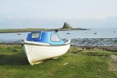 Castillo, bahía y barco de Lindisfarne fotografía de archivo