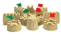 Castillo de arena con diversas banderas del color en superior aisladas en blanco Imágenes de archivo libres de regalías